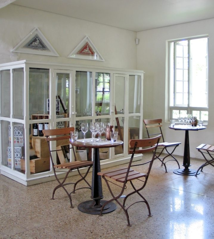 Tables constructed from oak vat tops on cast iron pedestals. Painted white antique display cabinet.